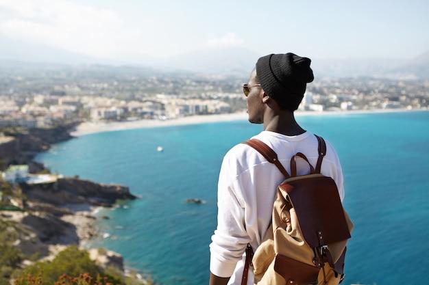 Rückansicht des modischen jungen männlichen rucksacktouristen, der oben auf dem berg meditiert und die schöne natur um ihn herum bewundert. nicht erkennbarer dunkelhäutiger mann, der blauen ozean aus der vogelperspektive betrachtet