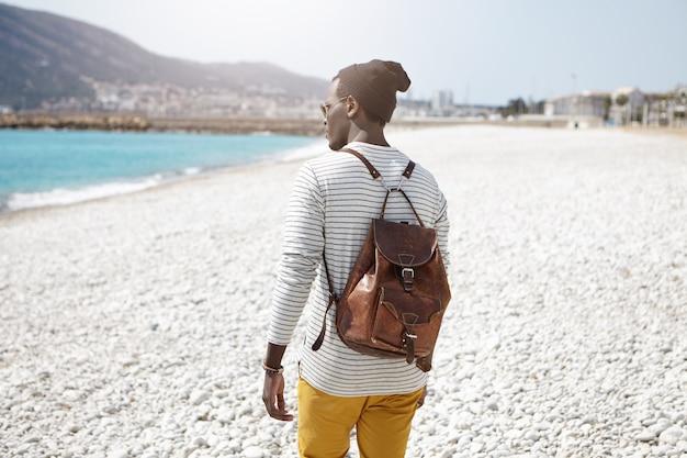Rückansicht des modischen schwarzen männlichen studenten, der braunen lederrucksack und stilvollen hut am warmen frühlingstag trägt, der schönen spaziergang am strand hat