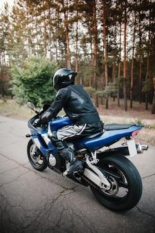 Rückansicht des motorradfahrers, der in helm mit unscharfem wald fährt