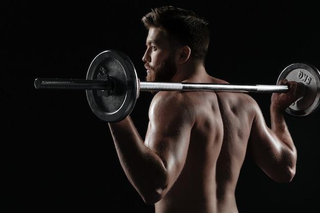 Rückansicht des muskulösen mannes mit langhantel. isolierter dunkler hintergrund