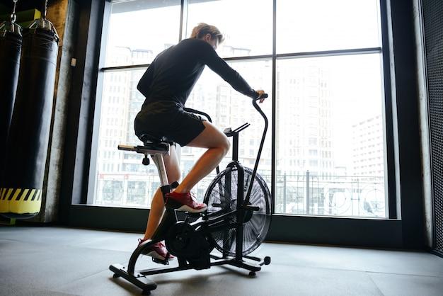 Rückansicht des muskulösen mannes unter verwendung des sich drehenden fahrrads