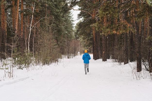 Rückansicht des nicht erkennbaren mannes in der blauen jacke, die im winterwald läuft