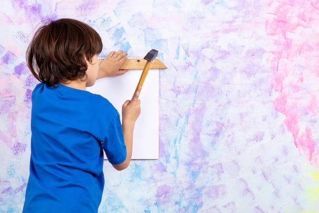 Rückansicht des niedlichen jungen im blauen t-shirt, das mit hammer an bunter wand arbeitet
