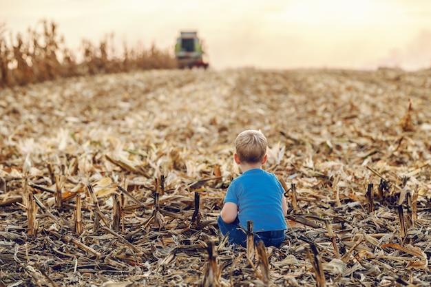 Rückansicht des niedlichen kleinen bauernjungen, der auf maisfeld hockt und spielt