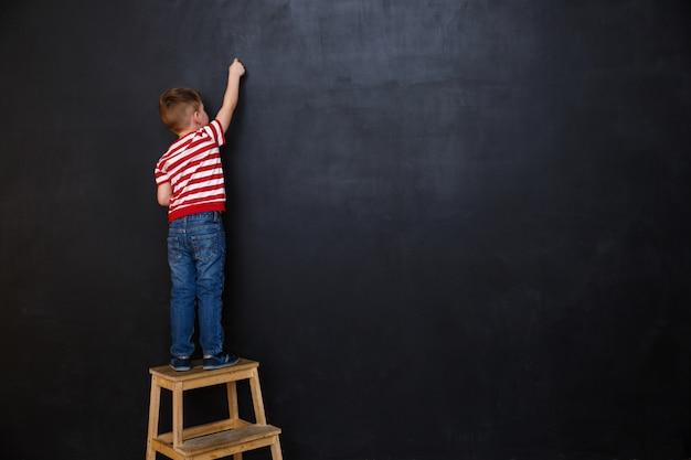 Rückansicht des niedlichen kleinen jungen, der mit kreide schreibt