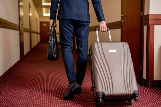 Rückansicht des niedrigen abschnitts des eleganten geschäftsmannes mit koffer und handtasche, die entlang korridor bewegen, während hotel verlassen