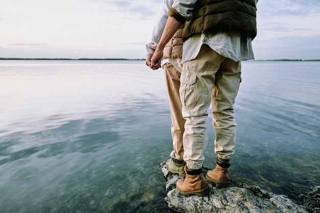 Rückansicht des niedrigen abschnitts des jungen verliebten paares, das nahe beieinander auf großem stein durch wasser steht, sich entspannt und einsamkeit genießt