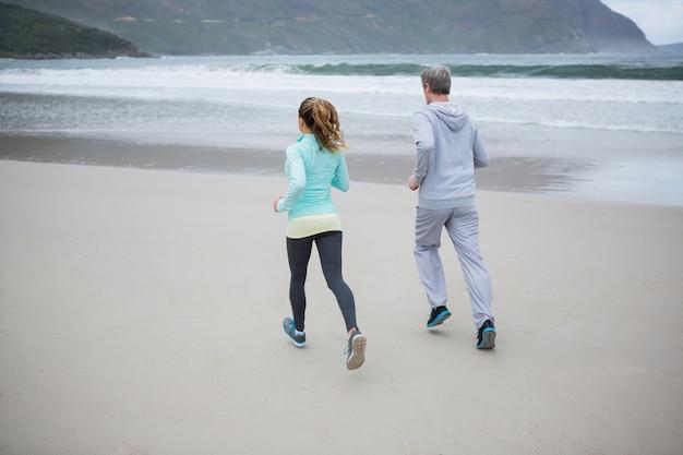 Rückansicht des paares, das am strand joggt