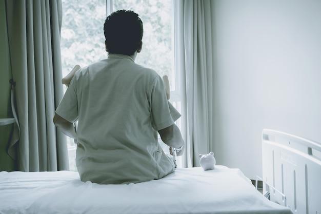 Rückansicht des patientenmannes bein benutzt krücken, um nach der operation zu gehen, gebrochene knochen mit rosa sparschwein
