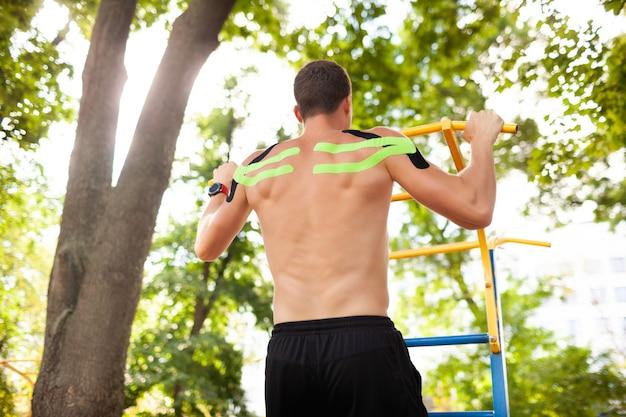Rückansicht des professionellen männlichen athleten mit buntem kinesiologischem taping auf dem rücken, das klimmzüge auf sportplatz im freien übt. sport und rehabilitation, kinesiotherapie-behandlungskonzept.