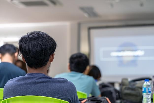 Rückansicht des publikums, das dem sprecher auf der bühne im konferenzsaal oder in der seminarsitzung zuhört