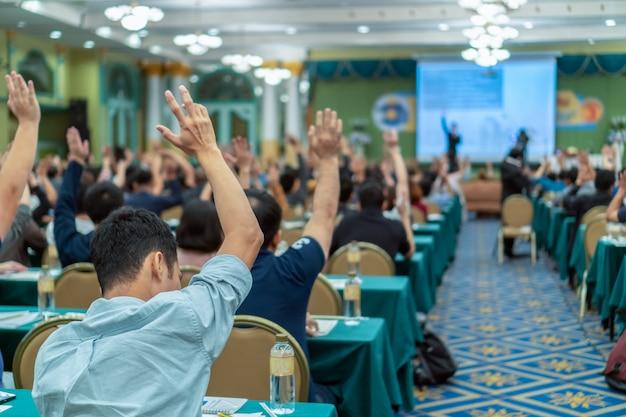 Rückansicht des publikums zeigt hand, um die frage vom sprecher auf der bühne zu beantworten