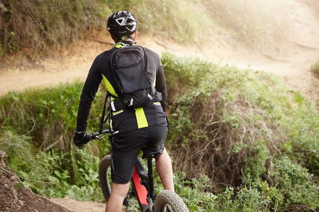 Rückansicht des radfahrers in der schwarzen kleidung, die elektrisches fahrrad in ländlichem hügeligem gebiet reitet