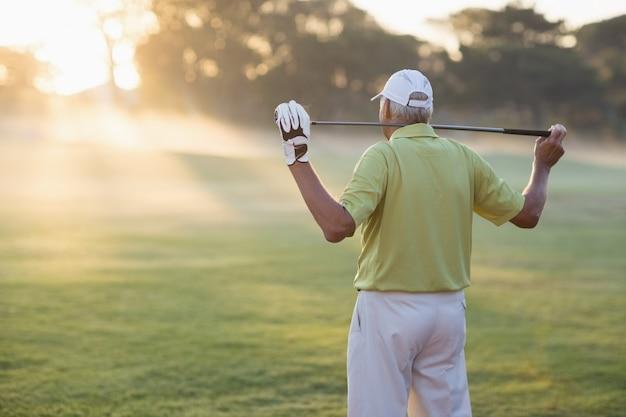 Rückansicht des reifen golfers, der golfschläger trägt