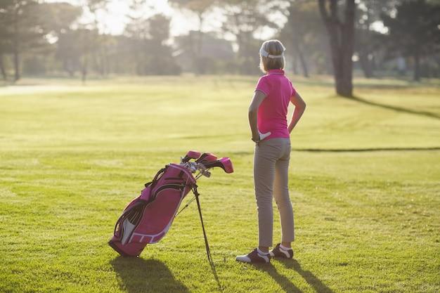 Rückansicht des reifen golfers mit den händen auf der hüfte