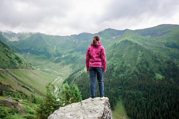 Rückansicht des reisenden der jungen frau, der auf felsenkante zwischen herrlichen grünen bergen steht