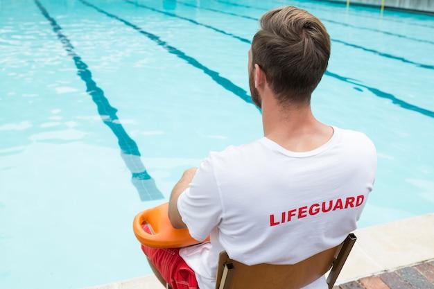 Rückansicht des rettungsschwimmers, der auf stuhl mit rettungsboje am pool sitzt