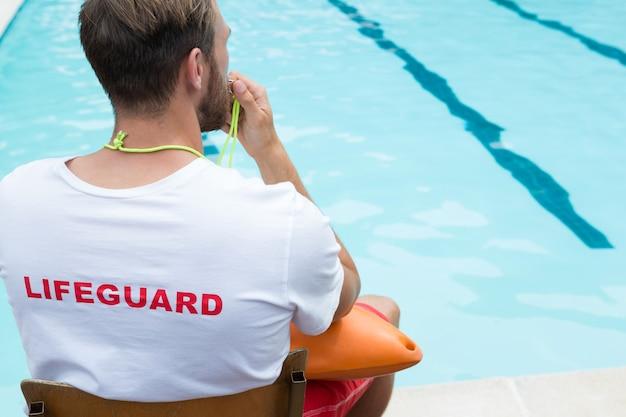 Rückansicht des rettungsschwimmers, der auf stuhl sitzt und am pool pfeift