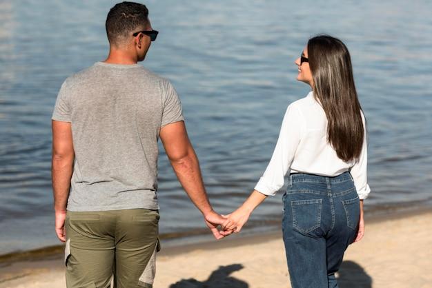 Rückansicht des romantischen paares, das hände am strand hält