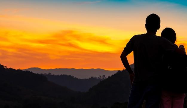 Rückansicht des romantischen paares, das schönen sonnenuntergang über bergschicht beobachtet