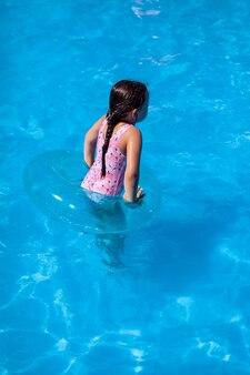 Rückansicht des rückens eines mädchens in einem rosa badeanzug, das mit einem aufblasbaren kreis in der hotelpo...
