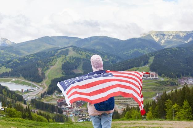 Rückansicht des schlanken aktiven touristen, der freizeitaktivitäten liebt, wandern, us-flagge halten, ihren rücken damit bedecken, berge betrachten