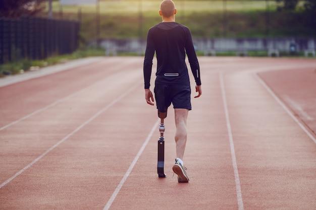 Rückansicht des schönen kaukasischen behinderten jungen mannes mit künstlichem bein und gekleidet in shorts und sweatshirt, die auf rennstrecke gehen.