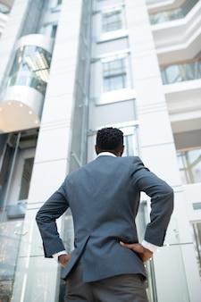 Rückansicht des schwarzen mannes in der jacke, die mit den händen auf den hüften im modernen geschäftszentrum steht