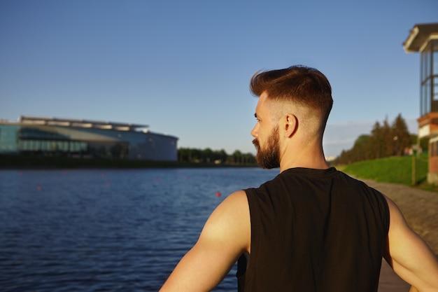 Rückansicht des selbstbestimmten jungen unrasierten männlichen joggers im schwarzen ärmellosen oberteil, das draußen am fluss steht, in die ferne schaut, atem holt und sich nach intensivem lauftraining ausruht
