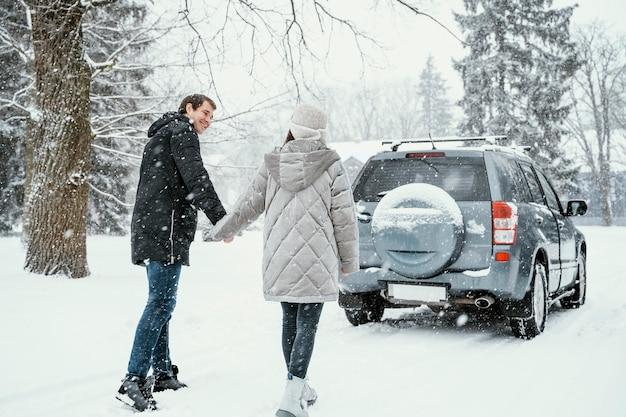 Rückansicht des smiley-paares, das den schnee während eines roadtrips genießt