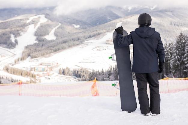 Rückansicht des sportlers mit snowboard, der die fahrspur beobachtet