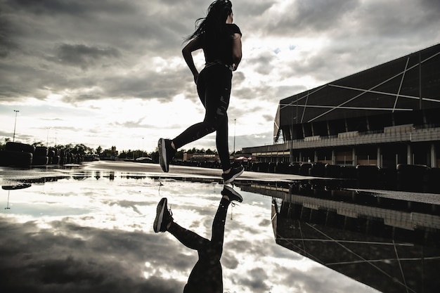 Rückansicht des starken sportlichen frauenläufers in bewegung. morgentraining im freien nach dem regen. frau, die sich auf einen marathon vorbereitet.