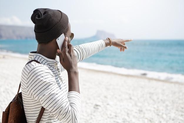 Rückansicht des stilvollen afroamerikanischen mannes, der finger zum ozean zeigt, während er am strand steht und auf dem mobiltelefon spricht, etwas interessantes im wasser bemerkt. menschen und moderne technik