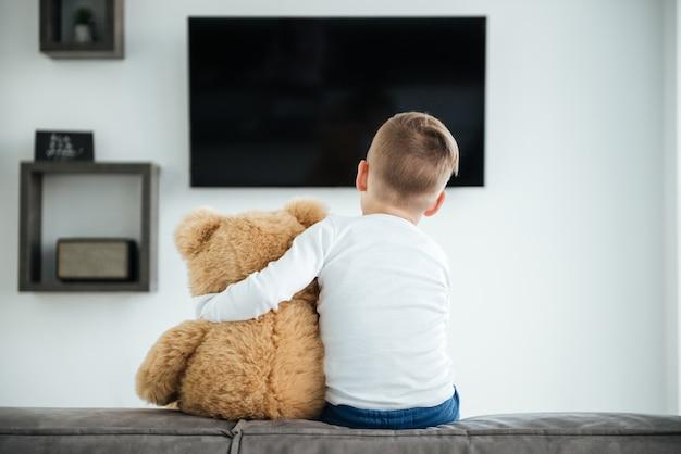 Rückansicht des süßen kleinen jungen, der auf dem sofa sitzt, mit teddybär, der zu hause auf die eltern wartet und fernsieht. schauen sie ins fernsehen.