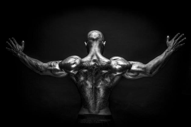 Rückansicht des tätowierten bodybuilders mit ausgestreckten armen