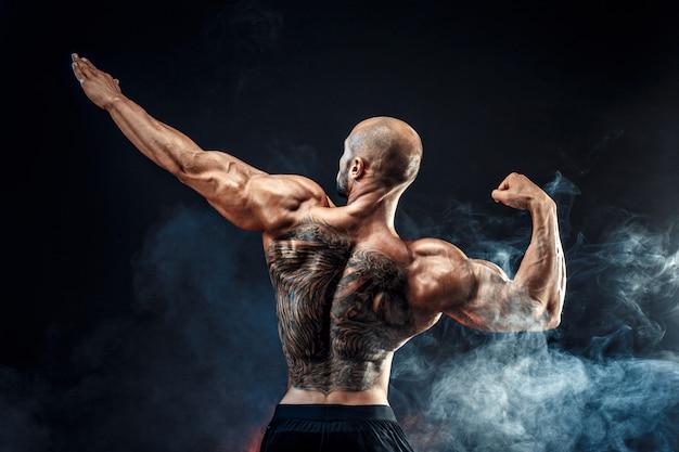 Rückansicht des tätowierten muskulösen mannes, der mit arm oben aufwirft