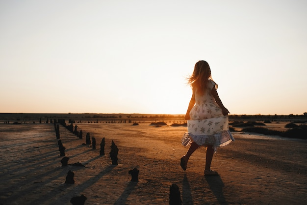 Rückansicht des tanzenden kindes auf dem sand am abend mit sonnenuntergang