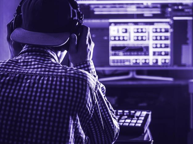 Rückansicht des toningenieurs in snapback und mit kopfhörern auf dem kopf, farbe des 2020-jahres-trends, klassische blautöne