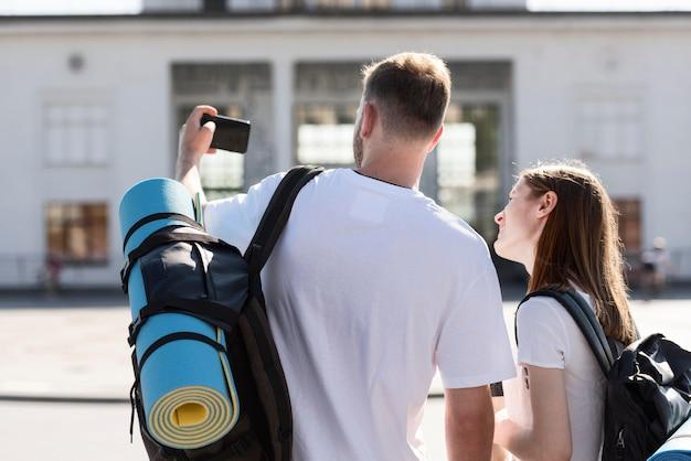 Rückansicht des touristenpaares draußen mit rucksäcken, die selfie nehmen