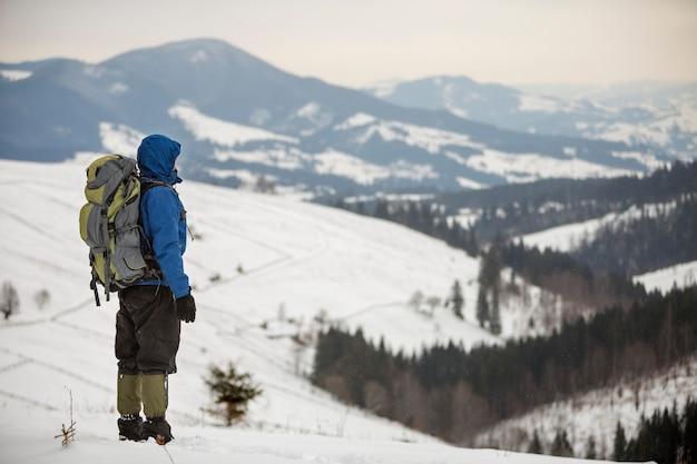 Rückansicht des touristenwanderers in der warmen kleidung mit dem rucksack, der auf berg steht