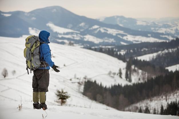 Rückansicht des touristenwanderers in warmer kleidung mit rucksack, der auf berg steht