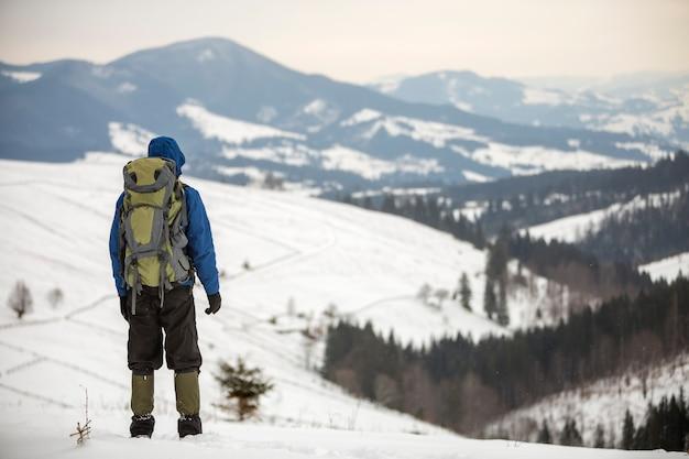 Rückansicht des touristischen wanderers in der warmen kleidung mit dem rucksack, der auf berglichtung auf kopienraumhintergrund des holzigen bergrückens und des bewölkten himmels steht.
