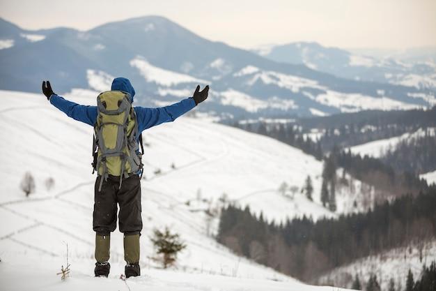 Rückansicht des touristischen wanderers in der warmen kleidung mit dem rucksack, der mit den erhobenen armen auf der bereinigung auf kopienraumhintergrund des holzigen bergrückens und des bewölkten himmels steht.