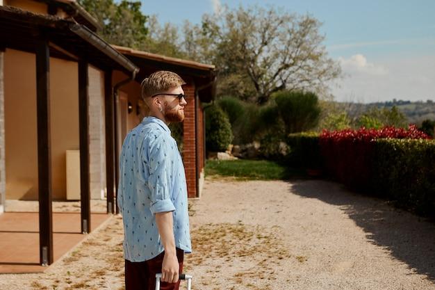 Rückansicht des trendigen bärtigen jungen mannes, der sonnenbrille und sommerkleidung trägt, die koffer trägt