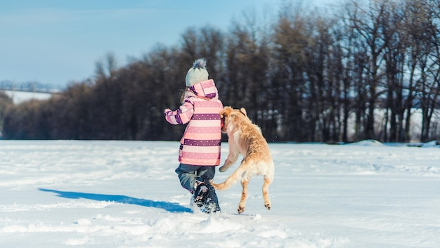 Rückansicht des verspielten hundes und des reizenden mädchens draußen im winter