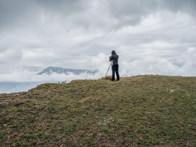 Rückansicht des wanderers, der das meer durch eine slr-kamera fotografiert, während er bei schwierigen wetterbedingungen auf einer klippe steht.