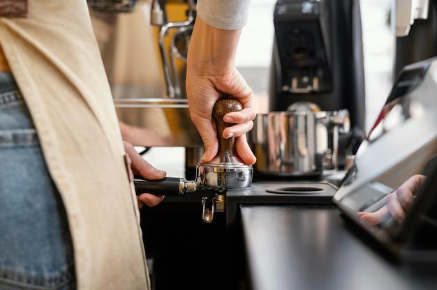 Rückansicht des weiblichen barista unter verwendung der kaffeemaschine