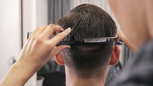 Rückansicht des weiblichen friseurhaarschnitts, der männliche frisur macht.