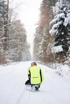 Rückansicht des weiblichen läufers, der ihre schnürsenkel bindet