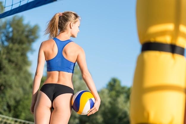 Rückansicht des weiblichen volleyballspielers auf dem strand, der ball hält